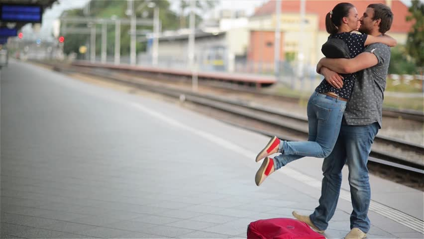 Young couple happy to meet again in the train station, girl runs to meet her boyfriend and throws a suitcase, twist on hands | Shutterstock HD Video #19608823