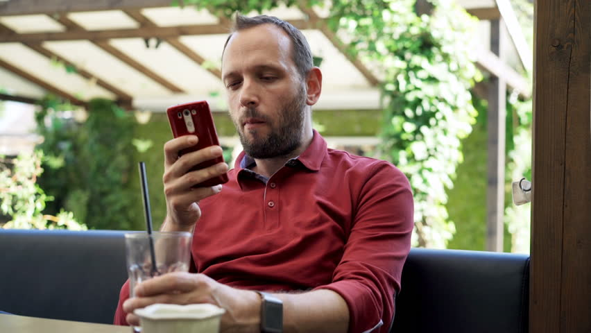 Young man using smartphone, drinking and eating snack in cafe  | Shutterstock HD Video #19616752