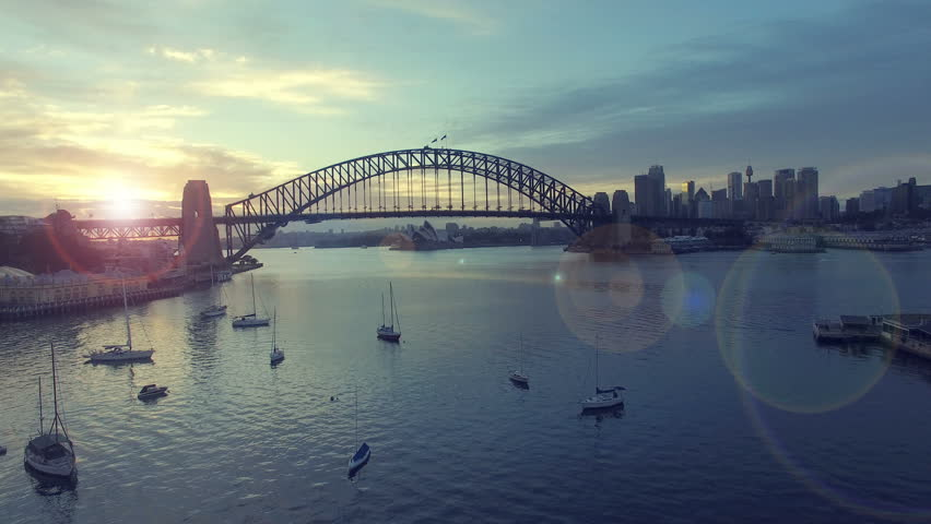 4k aerial footage b-roll of Sydney Harbour Bridge during sunrise. Cinematic look and lens flare effect.