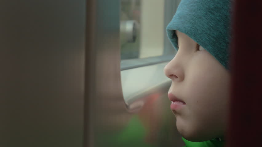 Close-up shot of a sad little boy in hat looking through the window of a moving train | Shutterstock HD Video #19649512