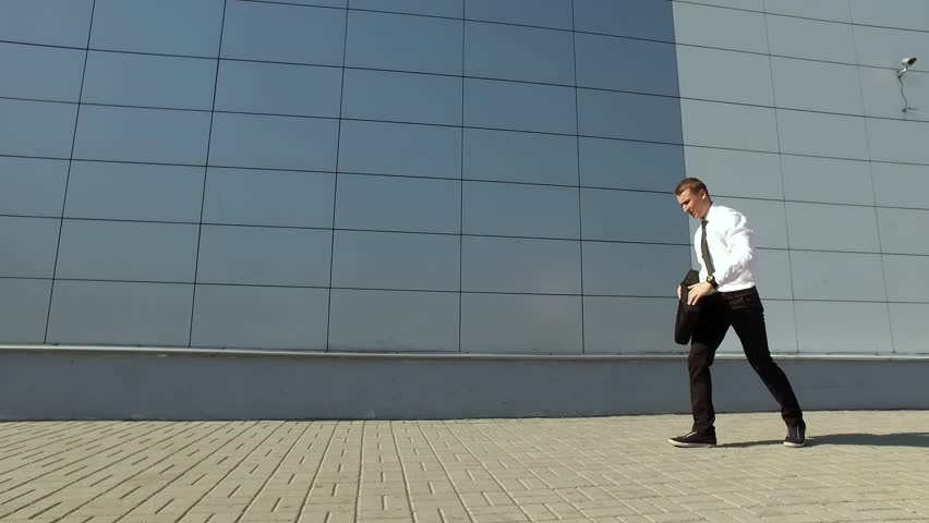 Businessmen looks at his watch and doing back flip in slow motion | Shutterstock HD Video #19668232