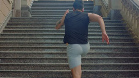 Man run up stairs in slow motion. Fitness man running upstairs. Man run up steps on staircase. Runner climbing stairs. Sport workout on stairs