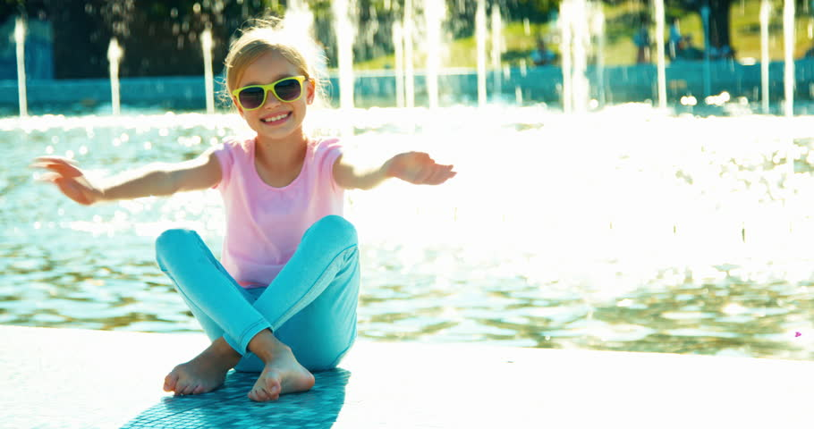 Portrait child girl 7-8 years in sunglasses sitting relaxing near fountain smiling at camera and waving hand | Shutterstock HD Video #19673830