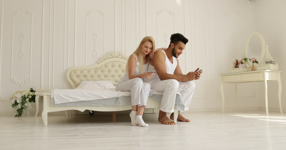 Couple using smart phone sitting bed mix race man woman embrace smile morning bedroom slow motion #19678870