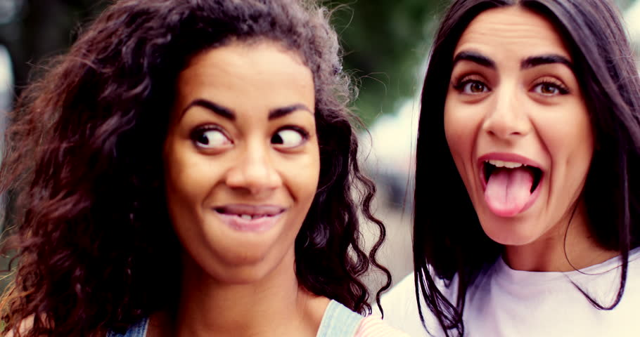Two vivacious young women goofing around pulling funny faces  close up head shots side by side