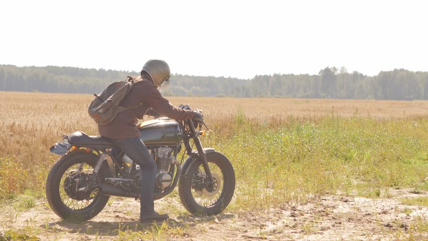 A man on the vintage custom cafe racer riding in a field. | Shutterstock HD Video #19689532