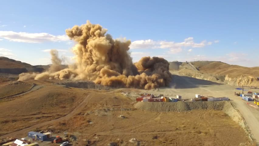Aerial view A massive explosion rocks in desert. Dirt and metal shards into the air