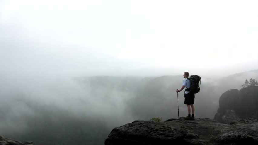 Alone tourist with big backpack stand on cliff edge and watching into deep valley bellow. spring weather.   | Shutterstock HD Video #19694857