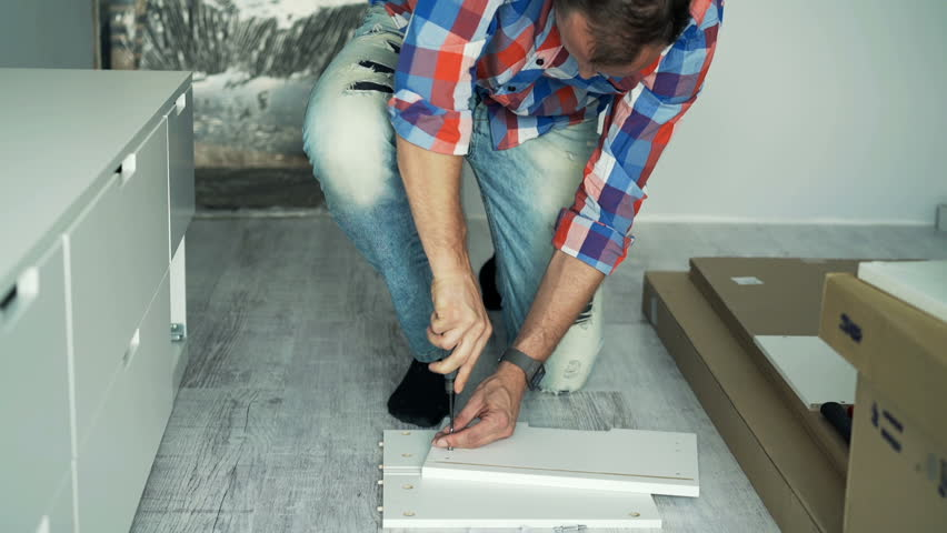 Young man with instruction matching furniture with screwdriver on floor at home  | Shutterstock HD Video #19697290