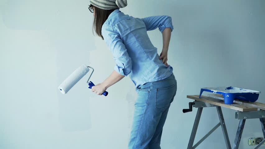 Hipster woman having back pain while painting wall at her new home
