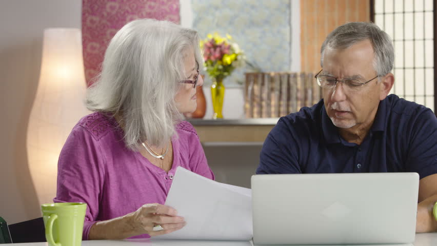 Senior aged couple looking at their bills