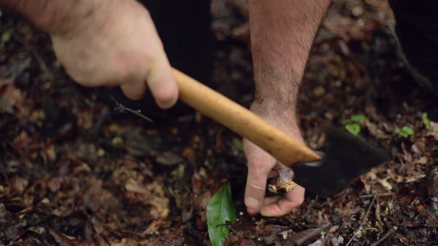 A male camper hammers a tent stake into the ground with a hatchet in slow motion, for a survival shelter.   Shutterstock HD Video #19714876
