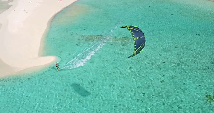 Aerial view young man kite surfing in tropical blue ocean