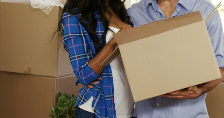 Young couple assisting each other while unpacking carton boxes in new house 4k   Shutterstock HD Video #19730776