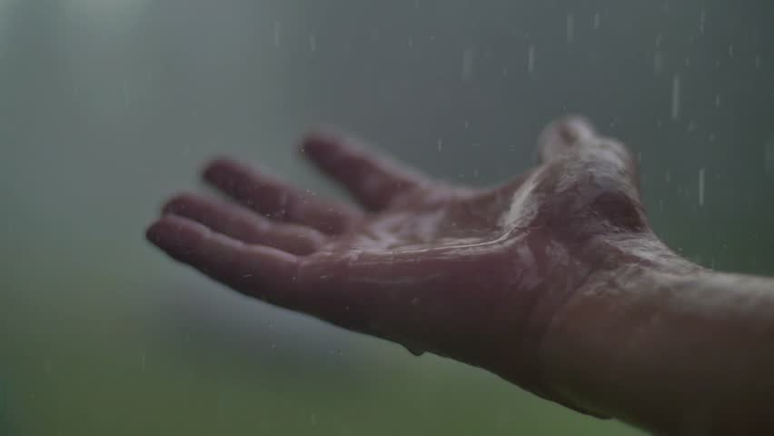 Man hand in the rain and hail