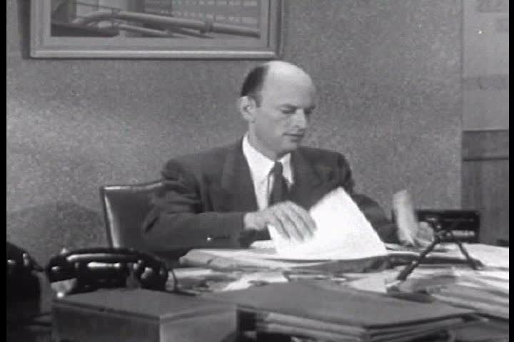 A secretary helps her harried boss find a contract on his messy desk in 1950. (1950s)