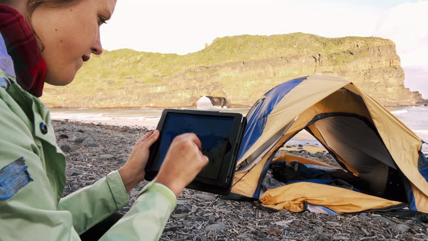 4k medium of Independent traveler woman using tablet device and looking at world map next to yellow tent with camping gear on an epic camping adventure.