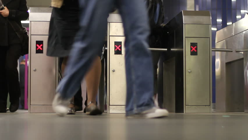 Passengers pass through subway turnstiles