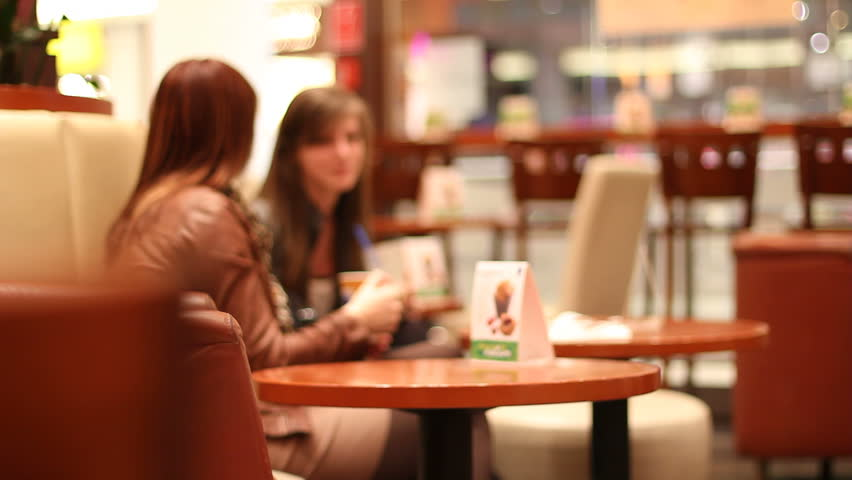 Two female friends enjoy coffee in cafe