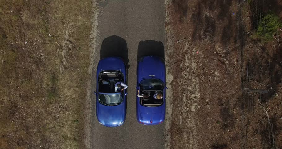 Two blue cabriolet on the road stopping and speaking  | Shutterstock HD Video #19775209