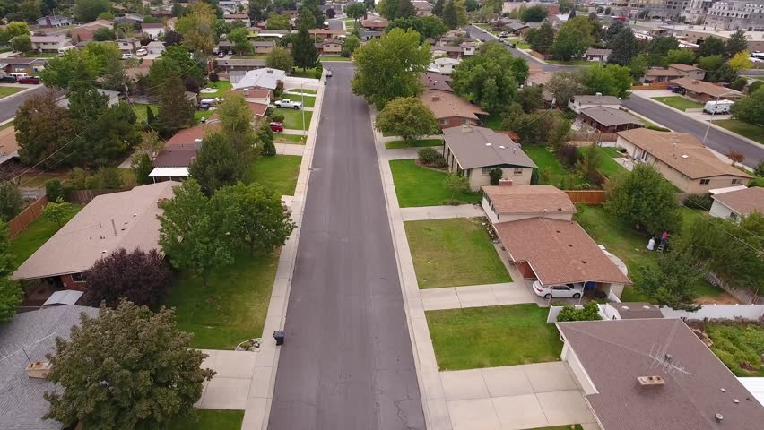 An aerial shot of cars driving on the roads in the busy city suburb neighborhoods | Shutterstock HD Video #19775626