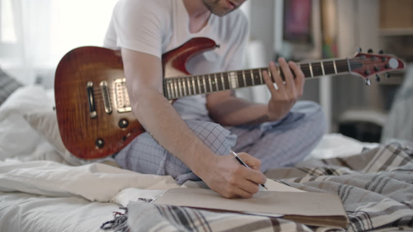 Man sitting on bed in pajamas and making some notes on paper while playing the guitar