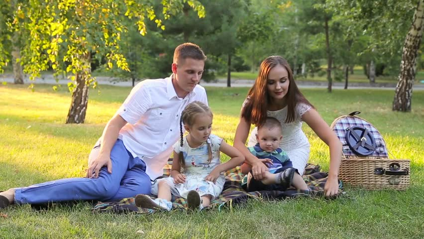 Young happy family of four on picnic in the park | Shutterstock HD Video #19788139