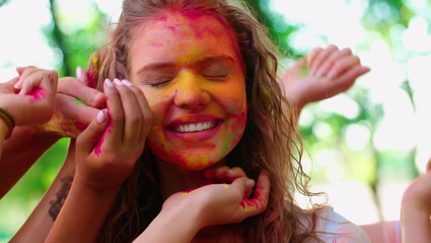 close-up of the model many hands stain the face of your friends with colors of Holi,slow motion