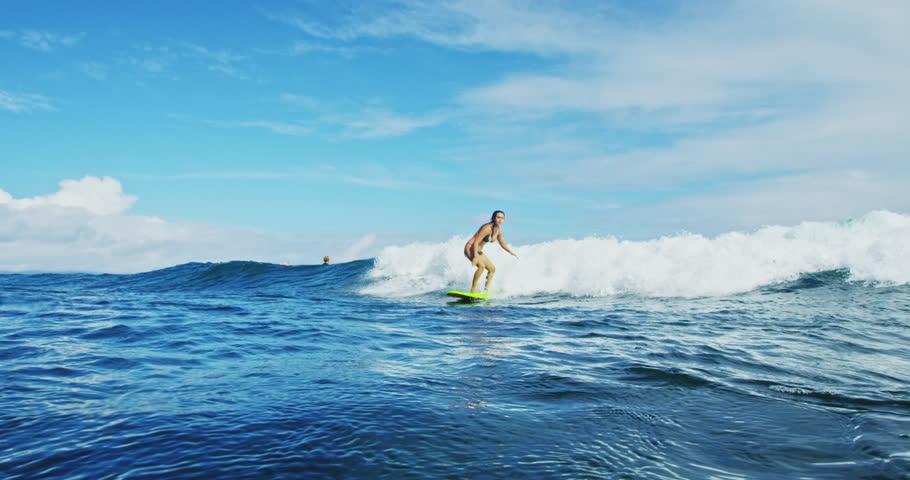 Surfer girl riding wave sprays water splashes camera. Shot on RED.   Shutterstock HD Video #19804351