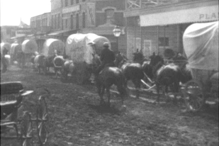 Wagon trains depart from St. Louis in the 1800s (as depicted in 1954). (1950s)