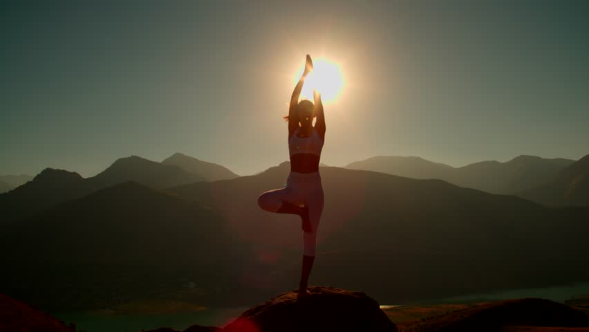 4K yoga in the mountains,the sunrise, a beautiful girl dressed in white ,pulls his hands to the sun #19827154