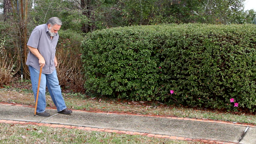 Old man walks down a sidewalk using a walking cane for support.