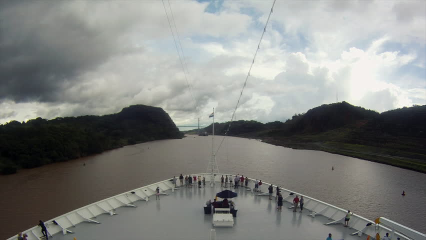 A ship heading from the Atlantic to the Pacific through the Panama canal. Goes under the Centennial Bridge in the Gatun Lake, then leaving the Pedro Miguel locks heading toward the Miraflores Locks.