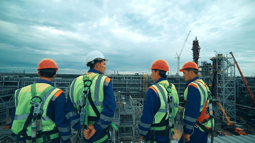 Workers at refinery as team discussing, industrial scene in background. #19847104