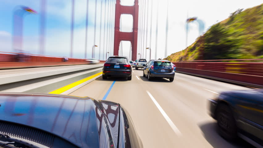 First person hyperlapse point of view, outside car, bonnet perspective crossing the Golden Gate Bridge from Marin into San Francisco driving thru traffic on a blue sky day. 4k 30fps time-lapse