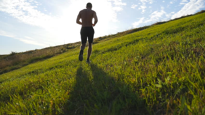 Young man running over green hill over blue sky background. Male athlete is jogging in nature at sunset. Sports runner jogging uphill outdoor at sunrise with flare. Cross-country training. Slow motion | Shutterstock HD Video #19855891