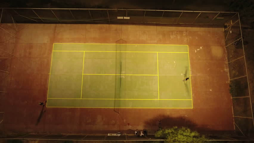 Top aerial shot of an illuminated tennis court at night, with players engaged in a game.   Shutterstock HD Video #19862395