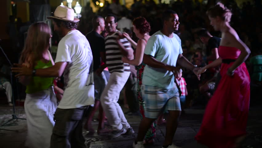 HAVANA, CUBA - AUGUST 15, 2016: Men and women are dancing passionate national dance salsa on the illuminated tourist street of Havana at night time