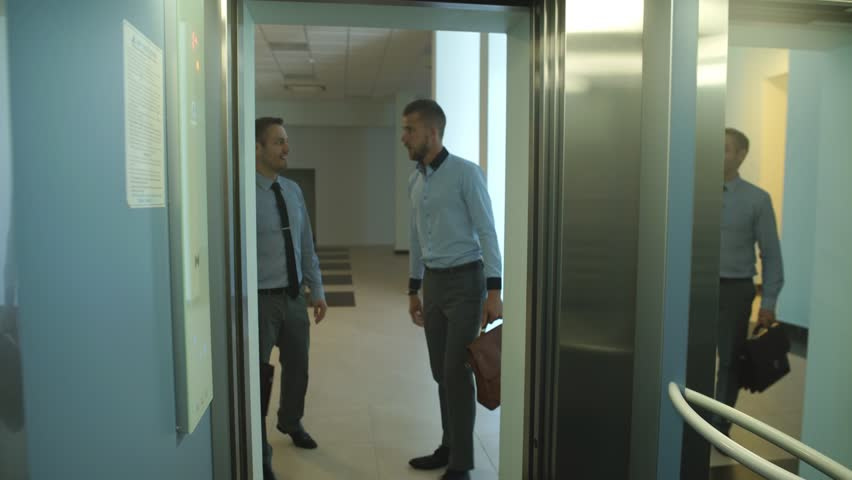 Two businessmen riding the Elevator and talking to | Shutterstock HD Video #19910242