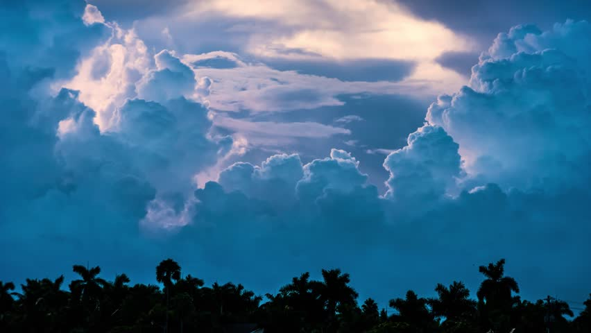 Epic storm tropical clouds forming over palm trees silhouettes at sunset. 4K UHD Timelapse.