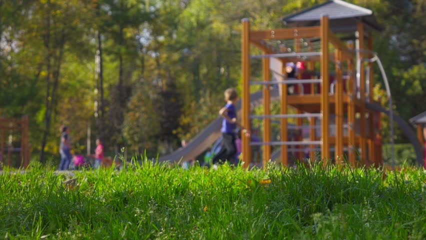Children and parents having fun on playground in park. Selective focus on foreground, slow motion. #19915240