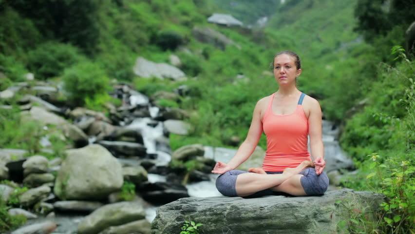 Woman meditating at tropical waterfall in Lotus pose Padmasana   Shutterstock HD Video #19915543