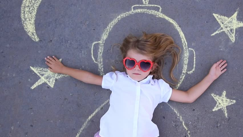 A little child is pretending to be an astronaut outside with creative chalk drawings of the stars and moon for an education or imagination concept.