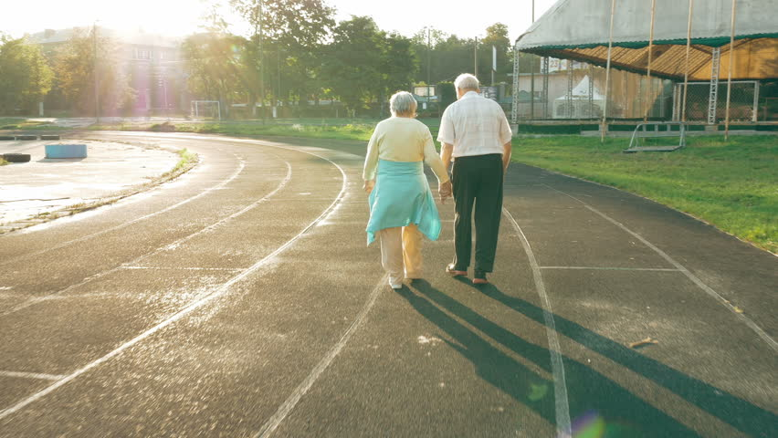 Senior couple taking a walk along the running track in summer. Healthy retirees enjoying morning walking on the stadium with camera lens flare. | Shutterstock HD Video #19927483