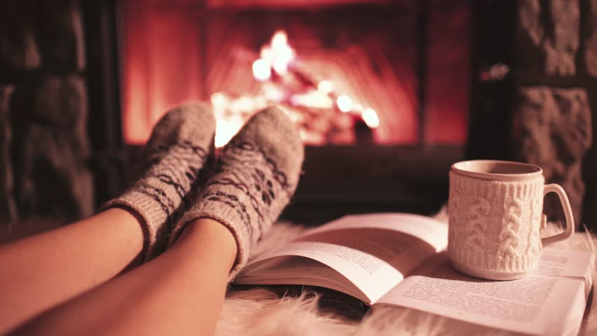 Woman Reading a Book by the Cozy Fireplace. 4K Stabilized shot. Young Unrecognizable Girl enjoying a Storybook by the warm Fireside With a Cup of Hot Drink in Ornamented Cup. Relaxed holiday evening.