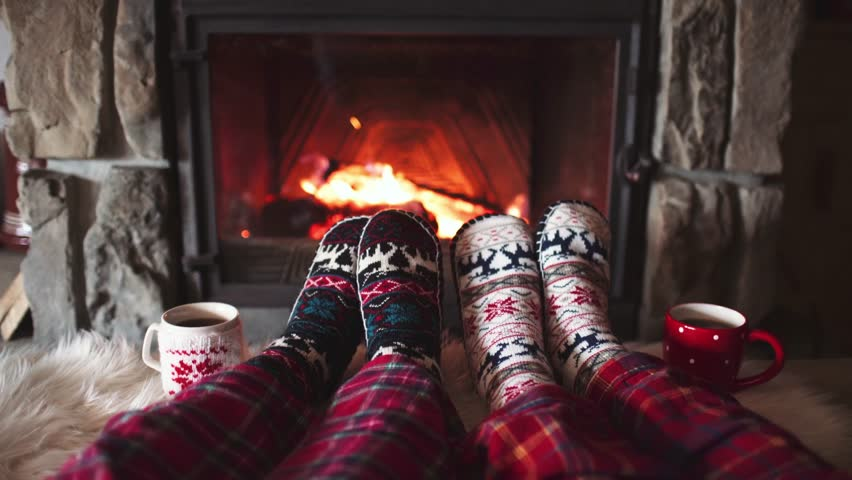 Feet in woollen socks by the Burning Christmas Cozy Fireplace. 4K. Couple relaxes by warm fire with cup of hot drink and warming up their feet. Winter and Christmas holidays concept.