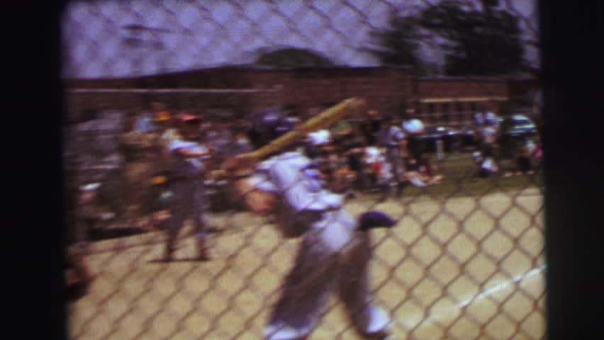 LYNBROOK, NEW YORK 1972: boy hits a fly ball in baseball outfielder catches and inning is over