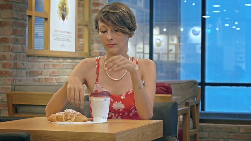 Beautiful young woman drinking coffee and eating delicious fresh croissant. | Shutterstock HD Video #19966543