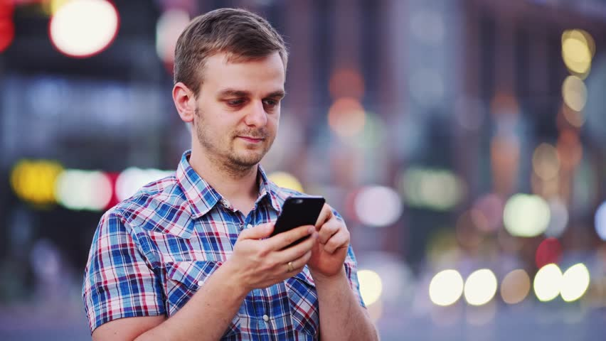 Man using smart phone at night in city. 4K. Handsome young Business Man texting, talking on smartphone outdoors. Professional millennial with cellphone, blurred Night Busy Street lights background. | Shutterstock HD Video #19973668