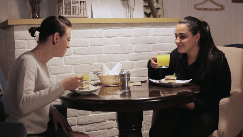 Two young women eating a cake, drinking a tea and talking in a cafe. Woomans have a positive mood, smiling and laughing   Shutterstock HD Video #19974997